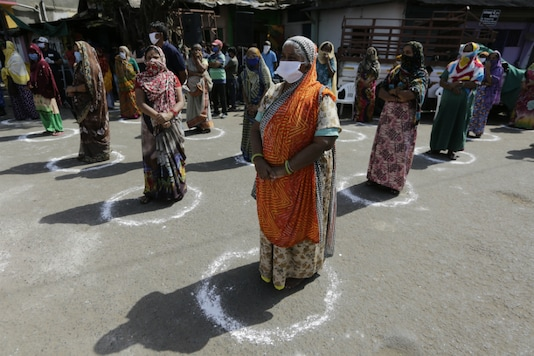 Women stand in marked circles to maintain distance as they wait to receive face masks, gloves and hand sanitizers during lockdown to control the spread of the new coronavirus in Ahmedabad, on April 11, 2020. (AP Photo/Ajit Solanki)