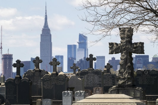 The Empire State building and the Manhattan skyline are seen behind the tombstones at Calvary Cemetery, on April 11, 2020, in the Maspeth neighborhood of the Queens borough of New York. (AP Photo/Mary Altaffer)