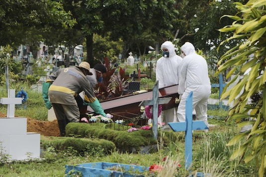 Funeral workers in protective clothes, and cemetery workers, place the coffin of Robson de Souza Lopes into his grave site the Parque Taruma cemetery in Manaus, Brazil. (Image: AP)