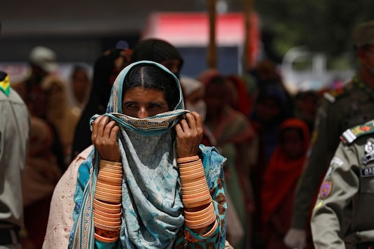 File photo of a woman covering her nose and mouth with scarf, as she along with others waits to receive cash from a country-wide Ehsaas Emergency Cash program, introduced by the Pakistani government for vulnerable families due to the ongoing spread of coronavirus disease (COVID-19), in Karachi. ( Reuters)