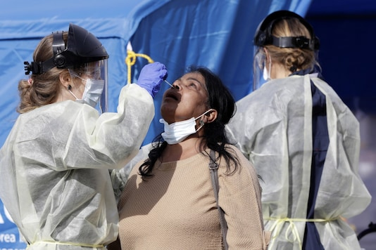 Medical staff test a shopper who volunteered at a pop-up community COVID-19 testing station at a supermarket carpark in Christchurch, New Zealand. (Image: AP)