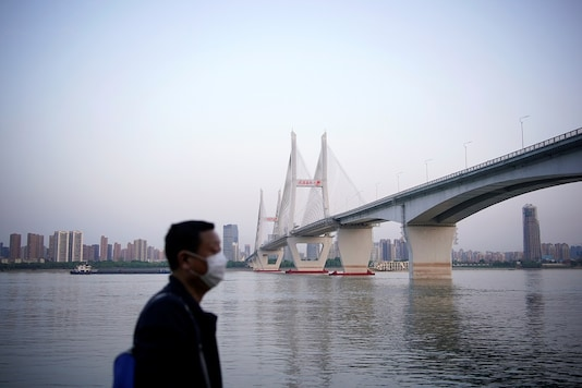 A man wearing a face mask is seen under a bridge of Yangtze river in Wuhan after the lockdown was lifted in Wuhan, capital of Hubei province and China's epicentre of the novel coronavirus disease (COVID-19) outbreak, April 15, 2020. REUTERS/Aly Song