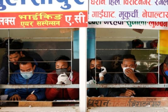 Workers wearing face masks sit inside a bus ticket counter, amid concerns about the spread of the coronavirus disease (COVID-19) outbreak, in Kathmandu, Nepal (REUTERS/Navesh Chitrakar)