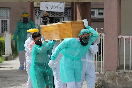 Health workers wearing protective gear move a body of a man who died from the coronavirus disease (COVID-19), outside an isolation ward at the Ayub Teaching Hospital in Abbottabad, Pakistan. (Reuters)