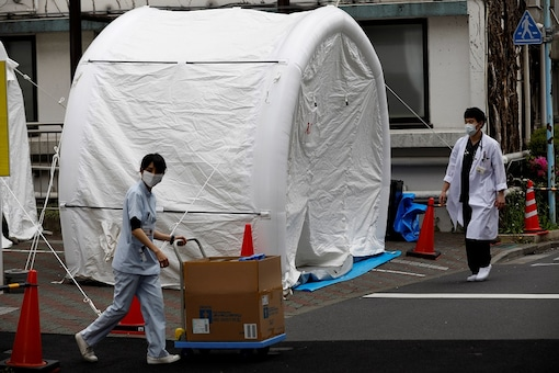 Medical workers walk by tents set up to test for the coronavirus disease (COVID-19) infection at Kawakita General Hospital in Tokyo, Japan. (Reuters)