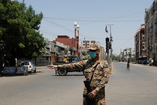 An army soldier gestures along a deserted road leading to a mosque during a lockdown after government limited congregational prayers and ordered to stay home, in efforts to stem the spread of the coronavirus disease (COVID-19), in Karachi, Pakistan. (Reuters)
