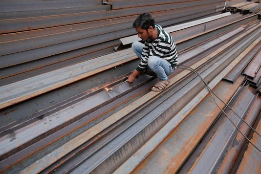 FILE PHOTO: A worker cuts iron rods outside a workshop at an iron and steel market in an industrial area in New Delhi, India, December 12, 2017. REUTERS/Adnan Abidi/File Photo