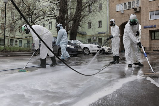 Specialists wearing protective gear spray disinfectant while sanitizing a street to prevent the spread of the coronavirus disease in Moscow, Russia April 18, 2020. (Sofya Sandurskaya/Moscow News Agency/Handout via REUTERS)