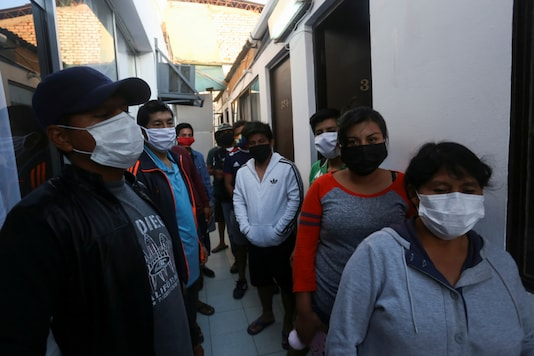 Peruvian citizens, stranded in Chile after the border was closed as preventive measure, gather at a hotel paid out by the Peruvian consular office, following the outbreak of the coronavirus disease (COVID-19) in Arica, Chile. (Reuters/Alexandre Infante)