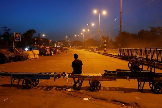 A man sits on a handcart erected across a road, as a blockade, during an extended nationwide lockdown to slow the spreading of coronavirus, in New Delhi. (REUTERS)