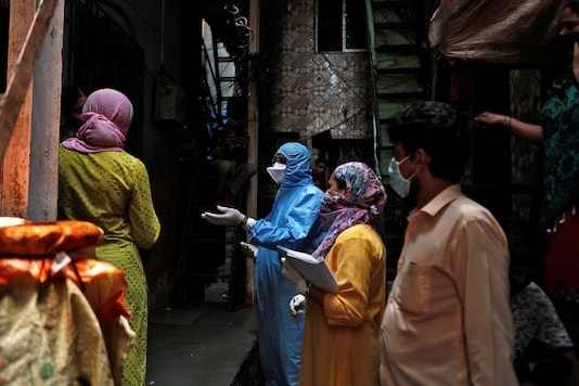 Health care workers conduct an inspection while asking residents who they live with and wether anyone is feeling unwell, during a nationwide lockdown, in Dharavi, Mumbai. (Reuters)
