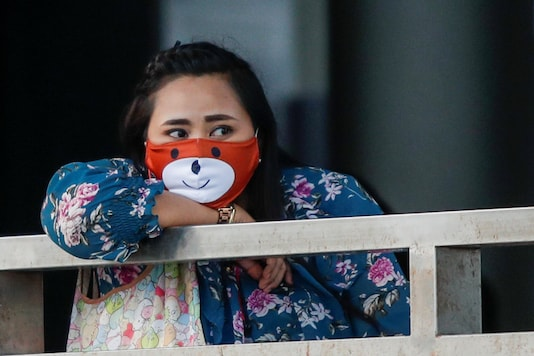A woman wears a protective face mask while commuting by boat, at the Chao Phraya river during the coronavirus disease (COVID-19) outbreak, in Bangkok, Thailand. (Image: Reuters)