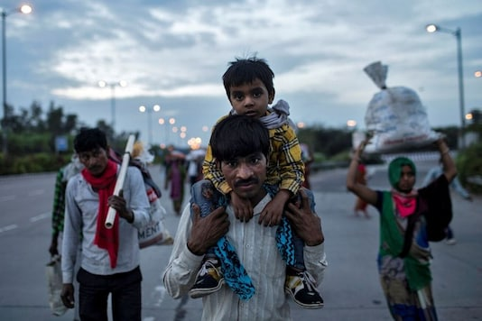 Dayaram Kushwaha, a migrant worker, carries his 5-year-old son, Shivam, on his shoulders as they walk along a road to return to their village, during a 21-day nationwide lockdown to limit the spreading of coronavirus, in New Delhi, India, March 26, 2020. REUTERS/Danish Siddiqui