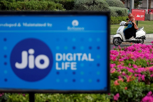A woman rides her scooter past advertisements of Reliance Industries' Jio telecoms unit in Ahmedabad. (REUTERS)