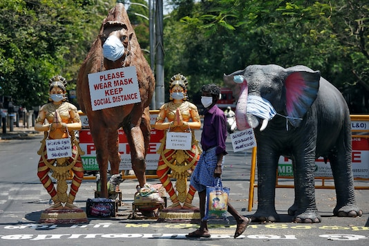 A man walks past replicas of animals and traditional dancers installed at a road crossing to create awareness about wearing masks, in Chennai. (Reuters)