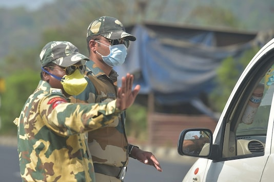 Police personnel wearing masks stop vehicles at a check post on Mumbai-Ahmedabad highway during the nationwide lockdown in Thane. (PTI)