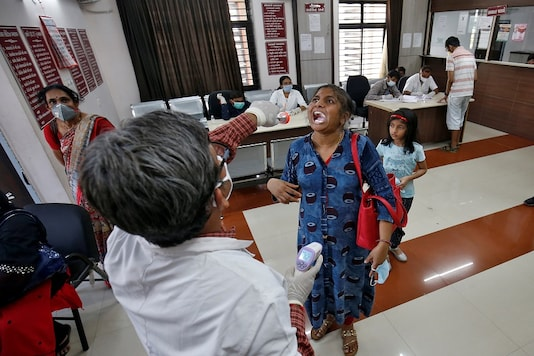A doctor examines a woman at a government office building on the outskirts of Ahmedabad in Gujarat. (REUTERS)