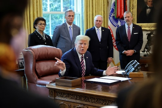 US President Donald Trump talks to reporters after signing the Paycheck Protection Program and Health Care Enhancement Act financial response to the coronavirus disease in the Oval Office at the White House in Washington. (Reuters)