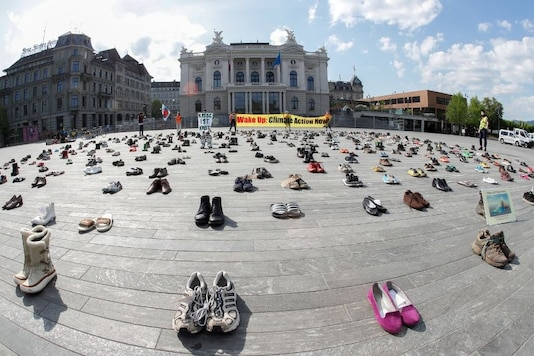 """Environmental activists of Swiss Klimastreik Schweiz movement hold banners, one of them reads: """"Crisis is crisis"""", after placing shoes in place of live participants to demonstrate against climate change, as the spread of the coronavirus disease (COVID-19) continues, in front of the opera house on the Sechselaeutenplatz square in Zurich, SwitzerlandREUTERS/Arnd Wiegmann"""