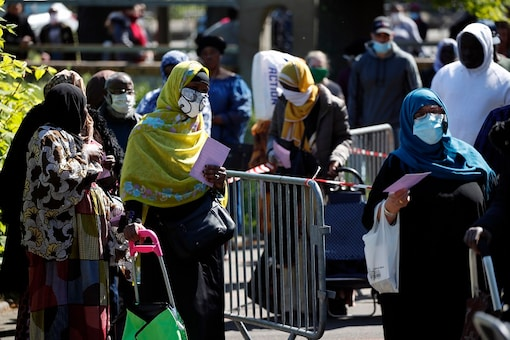 Residents arrive to collect soap, vegetables, fruits and other staples distributed by volunteers from community organizations in Clichy-sous-Bois, a suburb north of Paris.   (AP Photo/Francois Mori, File)