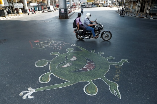 People ride past a graffiti on a road depicting the coronavirus in Mumbai. (Reuters)