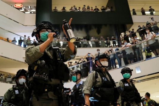 A riot policeman wearing face mask to avoid the spread of the coronavirus disease (COVID-19) holds a pepper spray as he tries to disperse anti-government protesters as they stage a rally at a shopping mall, in Hong Kong. (Reuters)