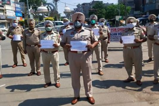Punjab police personnel pose with Harjeet Singh's name tag written on a paper to show solidarity.