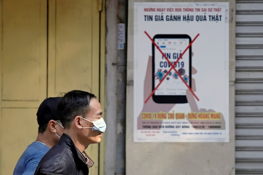 Men wear protective masks as they walk past a poster warning against the spread of 'fake news' online on the new coronavirus in Hanoi, Vietnam April 14, 2020. (Reuters/Kham)