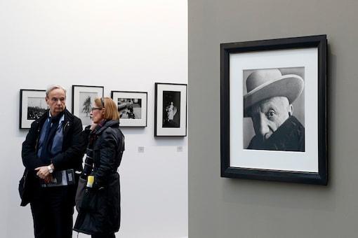 Visitors walk past a portrait of Pablo Picasso (Cannes, 1957) by photographer Irving Penn during a press visit of the Paris Photo art fair at the Grand Palais exhibition hall in Paris November 14, 2012.  REUTERS/Ben