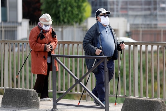 An elderly couple wear masks as they get some exercise on a bridge during the outbreak of the coronavirus disease (COVID-19) in Charenton-le-Pont near Paris, France  REUTERS/Charles Platiau - RC2CEG9Q2HOL