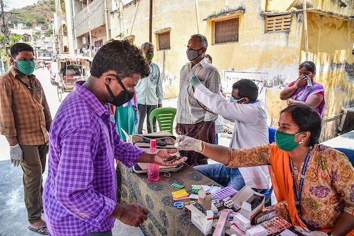 A man receives medicines as a healthcare worker examines a patient for COVID-19, during the nationwide lockdown to curb the spread of coronavirus, in Vijayawada. (PTI Photo)