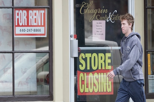 A man walks past a closed business, Wednesday in Chagrin Falls, Ohio.   (AP Photo/Tony Dejak)