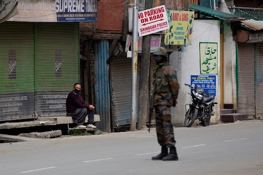 An elderly man enjoys the afternoon sun outside a closed shop as an Indian army soldier stands guard during a lockdown in Srinagar, Jammu and Kashmir. (AP)