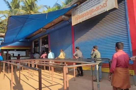 File photo: People queue up outside a liquor shop while strictly following social distancing protocols in Kerala.