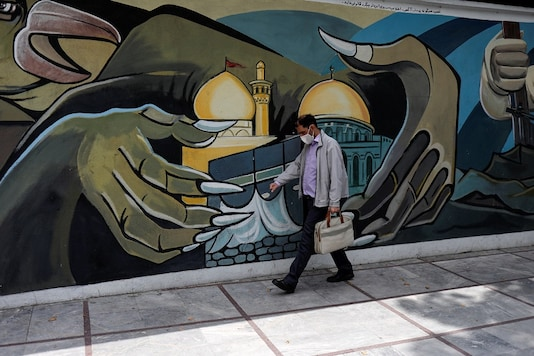 A man wearing a protective face mask walks past a Palestine mural on the wall following the outbreak of the coronavirus disease (COVID-19), in Tehran, Iran. (West Asia News Agency)/Ali Khara via REUTERS