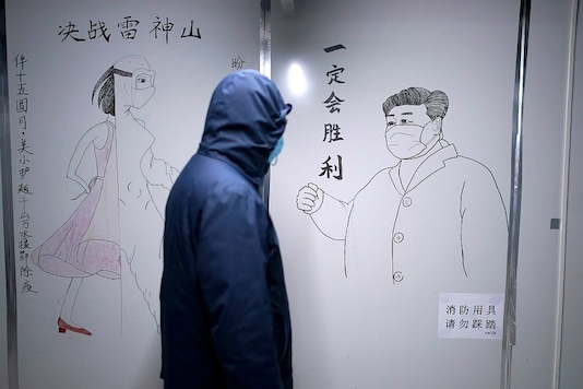 A staff member walks past a sketch of Chinese President Xi Jinping with a face mask on the wall of a closed ward inside the Leishenshan Hospital, a makeshift hospital for treating patients with the coronavirus disease (COVID-19), in Wuhan, Hubei province, China. (Reuters)
