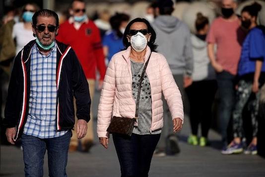 File photo of people in protective face masks walking on the Bridge of Segovia amid the coronavirus disease (COVID-19) outbreak, in Madrid, Spain. (Reuters)