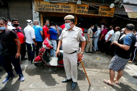 A policeman keeps tabs on people queuing up to buy liquor in Delhi. (Reuters)