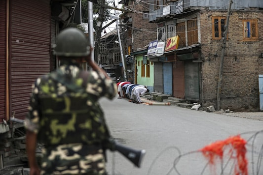 An Indian paramilitary soldier stands guard as Kashmiri Muslims offer Friday prayers on a street outside a local mosque during curfew like restrictions in Srinagar. (AP Photo/Mukhtar Khan)