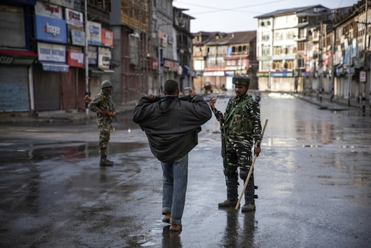 An Indian paramilitary soldier orders a Kashmiri to open his jacket before frisking him during curfew in Srinagar, Indian controlled Kashmir, . The beautiful Himalayan valley is flooded with soldiers and roadblocks of razor wire. The image was part of a series of photographs by Associated Press photographers which won the 2020 Pulitzer Prize for Feature Photography. (AP Photo/Dar Yasin)