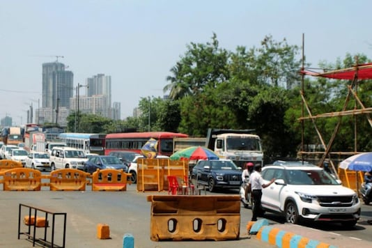 Traffic moves slowly at Dahisar Toll plaza on the Western Express Highway during the nationwide lockdown. (Image: PTI)