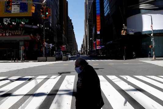 A man wearing a protective face mask crosses 7th Avenue in a nearly deserted Times Square in Manhattan during the outbreak of the coronavirus disease (COVID-19) in New York City, New York. (Image: Reuters)