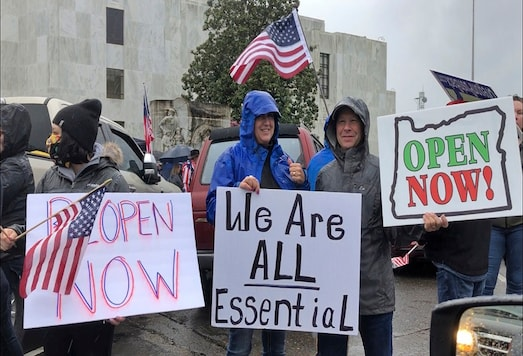 People hold signs protesting Oregon Governor Kate Brown's executive order that shut down much of the state's economy and imposed social distancing, in her effort to stem the spread of the coronavirus, rally outside the Oregon State Capitol in Salem. (AP)