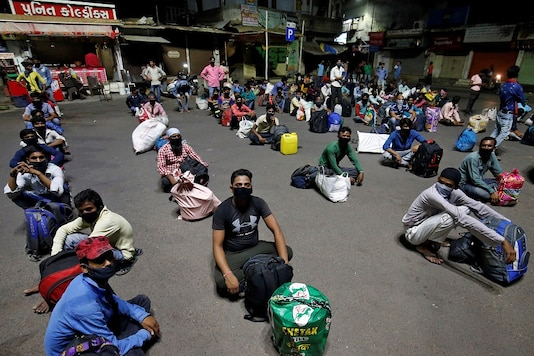 Migrant workers stranded in Gujarat due to a lockdown sit on a road as they wait to board a train that will take them to their home state of Bihar. (Reuters)