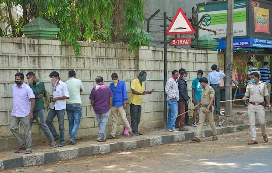 Police ask customers to follow social distancing rules as they stand in queue to buy liquor from a shop, amid COVID-19 lockdown in Bengaluru. (Image: PTI)