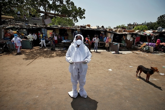 A health worker wearing a protective gear announces names of people who were tested positive for coronavirus and will be taken to a quarantine facility, at a slum area in Ahmedabad, India, May 5, 2020. (REUTERS/Amit Dave)