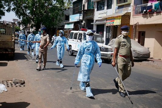 Security personnel wearing protective gear patrol a street in Ahmedabad. (PTI)