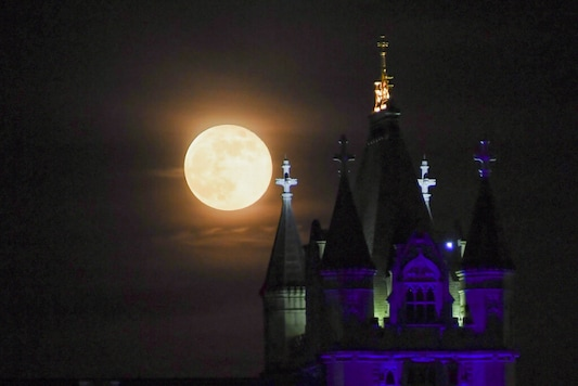 The supermoon rises behind Tower Bridge, in London, Thursday, May 7, 2020. The supermoon is a phenomenon that happens when the moon is at its closest point to the earth and looks larger than usual. (AP Photo/Alberto Pezzali)