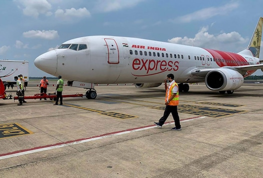 Airport staff carry out pre-departure checking of an Air India Express flight bound for UAE to bring back stranded Indian nationals, during the ongoing COVID-19 nationwide lockdown, in Kochi. (Image: PTI)