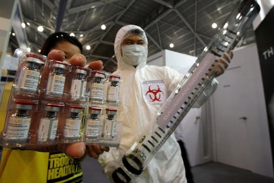 A man dressed in a bio-hazard protective gear poses while holding a mock syringe as a sales representative displays Imvamune, a smallpox vaccine developed by Bavarian Nordic to fight bioterrorism, during the Global Security Asia 2007 conference in Singapore, March 27, 2007. REUTERS/Vivek Prakash (SINGAPORE)